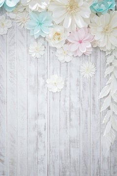 Pastel paper flower; cream, white, pink, green, blue with hand craft art on the white wood plate background.