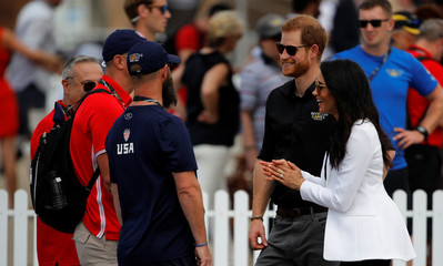 Britain's Prince Harry and Meghan, Duchess of Sussex, interact with people as they attend the Invictus Games Sydney 2018 Jaguar Land Rover Driving Challenge on Cockatoo Island, Sydney
