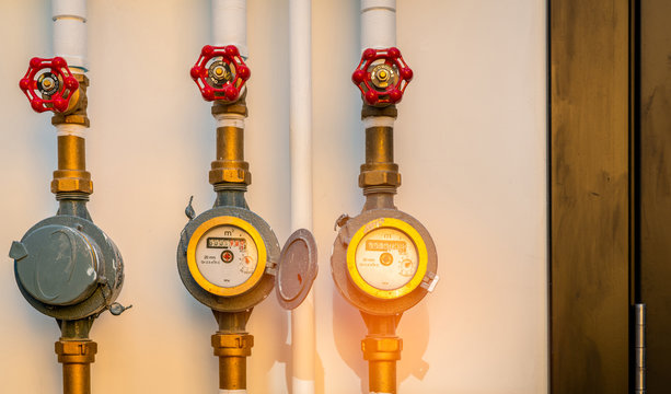Single water meter and valves on white concrete wall of house. Water consumption and bill concept. Water meters installed on the brass pipe of building. Residential water meters. Water meter reading.