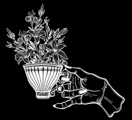 Hand holding a tea or coffee cup with lily flowers..