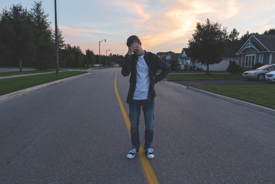 Upset teenager standing in the middle of a suburban street at sunset.