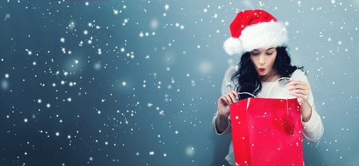 Happy young woman with santa hat holding a shopping bag on a gray background