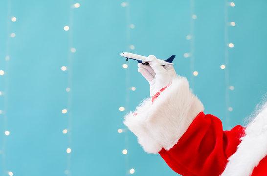 Santa holding a toy airplane on a shiny light blue background