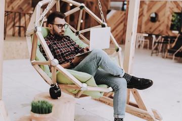 Laptop. Smartphone. Hanging Chair.Sit. Brainstorm.