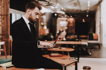 Business Suit. Laptop. Sit. Brainstorm. Young Guy.