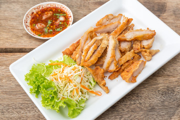 Fried Streaky Pork, vegetable and sauce (Thai food) in the white dish put on the wooden table.