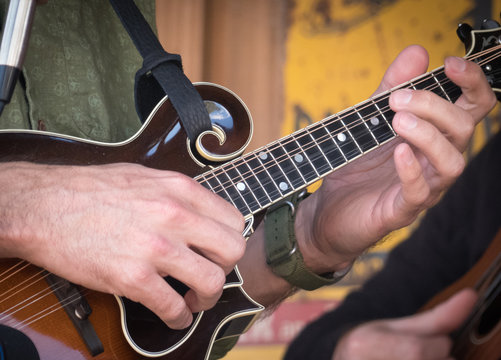 Closeup of a man's hands playing a brown wooden mandolin