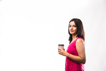 Pretty Indian young girl having coffee while wearing spectacles and speaking over phone, standing isolated over white background