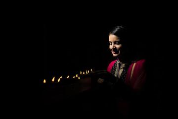 Pretty Young Indian girl arranging Diyas on Diwali Festival Night
