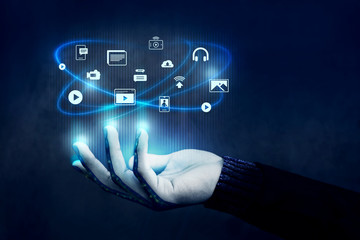 Digital Contents Management Concept. Many Icons Floating over a Human's Hand, Side view, Dark tone