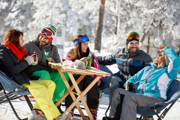 Skiers resting and refreshing with drink in cafe on ski terrain