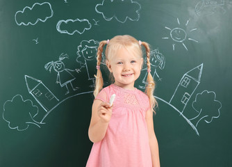 Little child holding chalk near blackboard with drawing of family