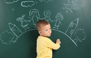 Little child drawing family with white chalk on blackboard
