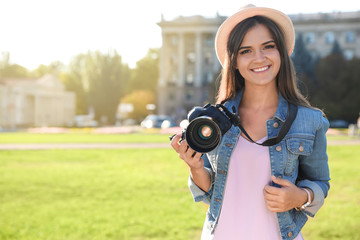 Young female photographer holding professional camera on street. Space for text
