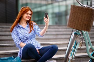 Woman making selfie in town near bike