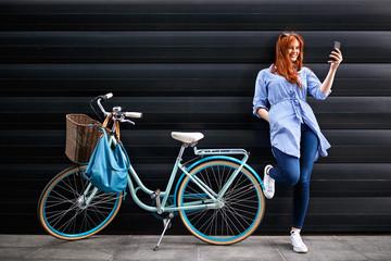 Female standing near bike and making selfie