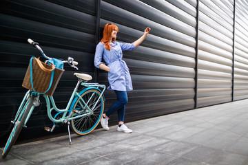 Urban girl taking selfie in city near bike