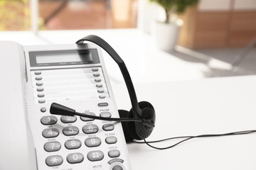 Headset and desk phone on table, space for text. Technical support concept