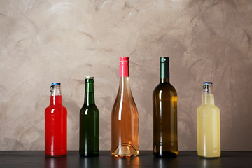 Bottles with different alcoholic drinks on table against color background