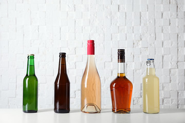 Bottles with different alcoholic drinks on table near white wall