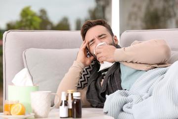 Ill man suffering from cough on sofa at home