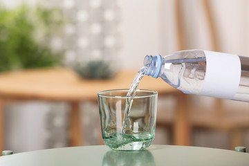 Pouring water from bottle into glass on table against blurred background