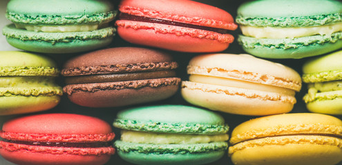 Flat-lay of sweet colorful French macaroon cookies stacked in rows, top view, wide composition