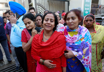 Family members cry after seeing the body of their relative after a commuter train traveling at high speed ran through a crowd of people on the railway tracks on Friday, outside a hospital in Amritsar