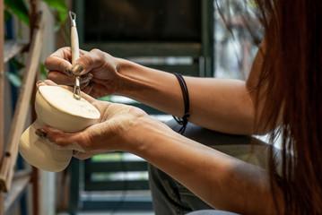 Detail of an artisan hands polishing a ceramic vase - 3