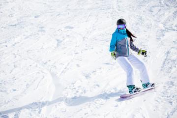 Photo of sportswoman snowboarding on snowy slope