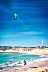 Girl doing kiteboarding under the rays of the sun on the beach of Los Caños de Meca, next to the lighthouse of Trafalgar, on the coast of Cadiz, southern Spain