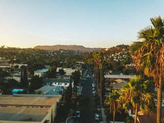 Beverly Hills street with palm trees at sunset in Los Angeles with Hollywood sign on the horizon.