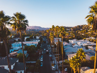 Fotomurales - Beverly Hills street with palm trees at sunset in Los Angeles with Hollywood sign on the horizon.