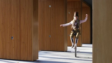 Wall Mural - Girl clown rides a unicycle then juggling a bike outdoors