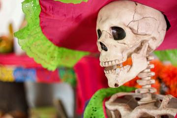 "A close up of a ""La Calavera Catrina"", a dapper skeleton dressed as Lady of the Dead, smoking a cigarette, in Valladolid, Yucatan, Mexico, for the Day of the Dead (Día de Muertos)."