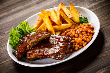 Tasty grilled ribs with french fries vegetables