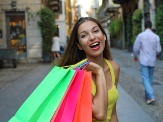 Close up of cheerful young woman holding shopper bags in Brera neighborhood, Milan, Italy