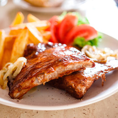 Tasty grilled ribs with french fries and vegetables
