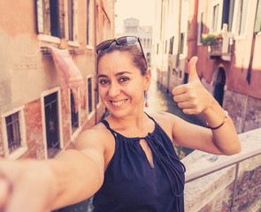 Woman tourist smiling and showing thumb up while taking a selfie at the canal in Venice Italy