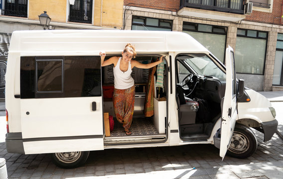 Hippie attractive young woman in her camper van excited ready to travel around Europe