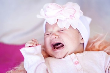 Cute newborn baby suffering from gas pain and crying. Gassy infant, colic gas treatment. Sad and upset infant concept image.