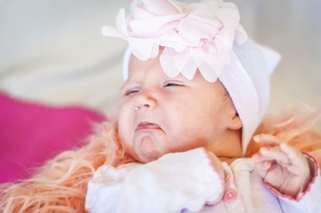 Cute newborn Caucasian baby about to start to cry, funny facial expression with bottom lip lower lip. Sad and upset infant child.