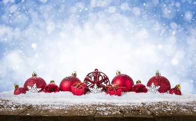 Christmas Background - Decorated Red Balls On Snow with snowflakesand stars on wooden desk