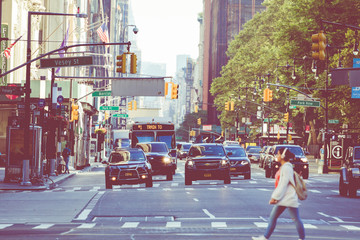 New York City street road in Manhattan at summer time, many cars, yellow taxis and busy people walk to work.