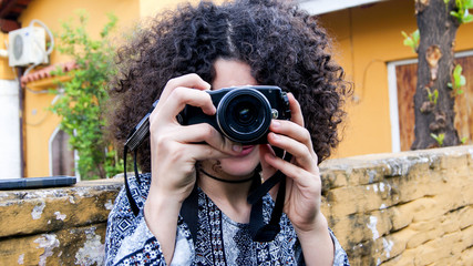 Young brunette girl with afro curly hair taking a photo with a photography proffesional camera in the street - lense looking at the camera - amateur woman photographer