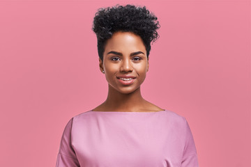 Happy African American businesswoman with positive smile, has crisp dark hair, rejoices having weekend and good rest after hard working exhausting week, isolated on pink wall