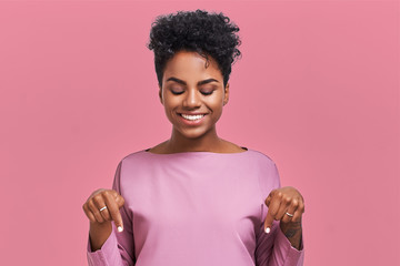 Funny surprised African American female looks with joyful eyes down and indicates as shows something, sees comic things, isolated over pink wall. Positive amazed young woman poses in studio
