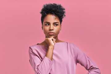 Gorgeous dark skinned young female with Afro hairstyle and confident look, poses for fashionable magazine, looks aside thoughtfully poses against pink studio background