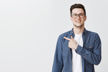 Polite and friendly handsome young caucasian man in glasses and blue shirt over t-shirt smiling joyfully as pointing left at copy space showing cool place for advertisement over grey wall Wall mural