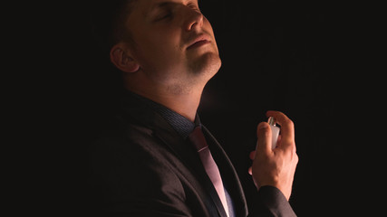 A young guy (man) is stifled by perfume, on a black background in a shirt. Concept: Perfume, Shirt, Spray, Handsome, Man, Beautiful, Black Background, Style.